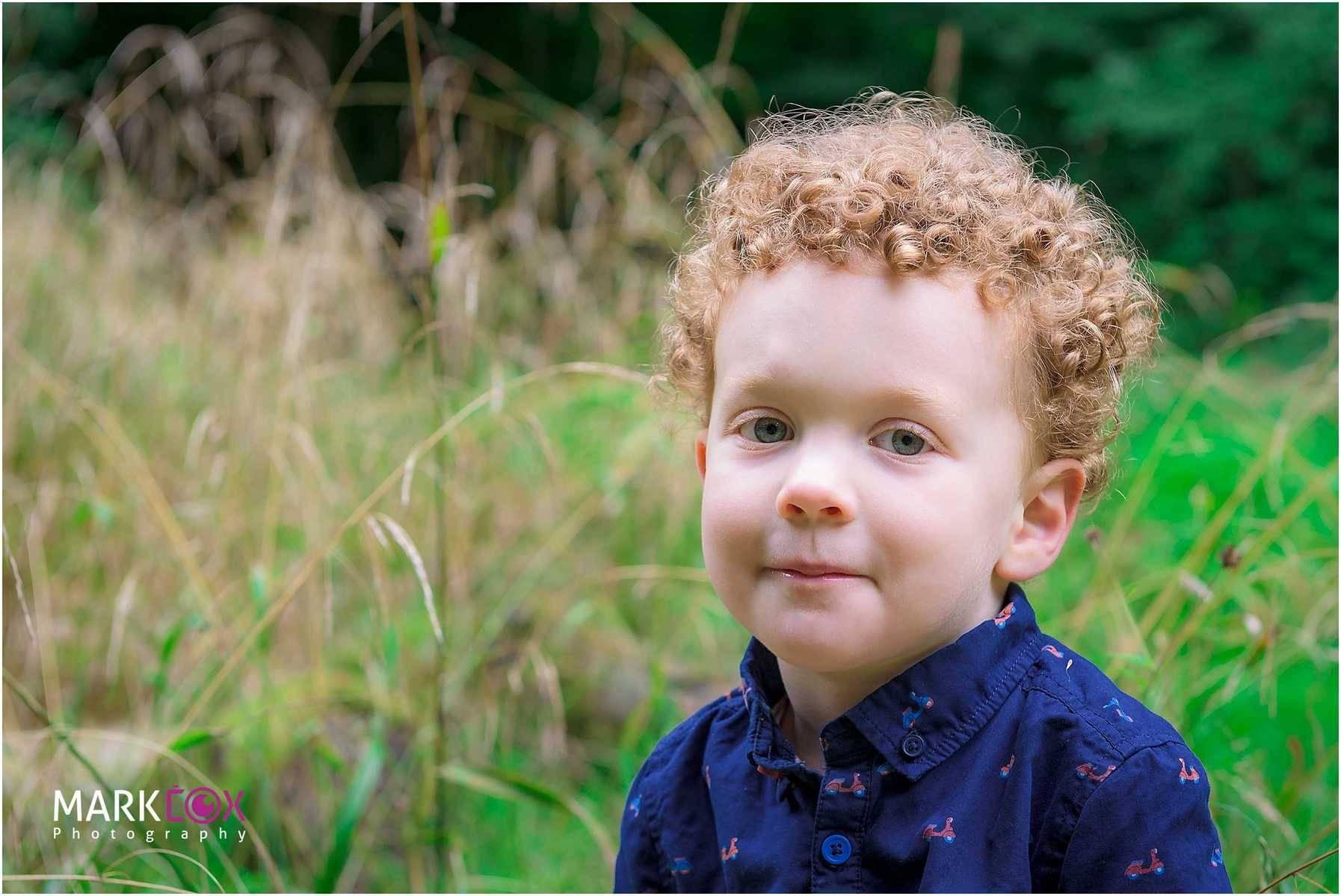 A little boy smiling having his photograph taken