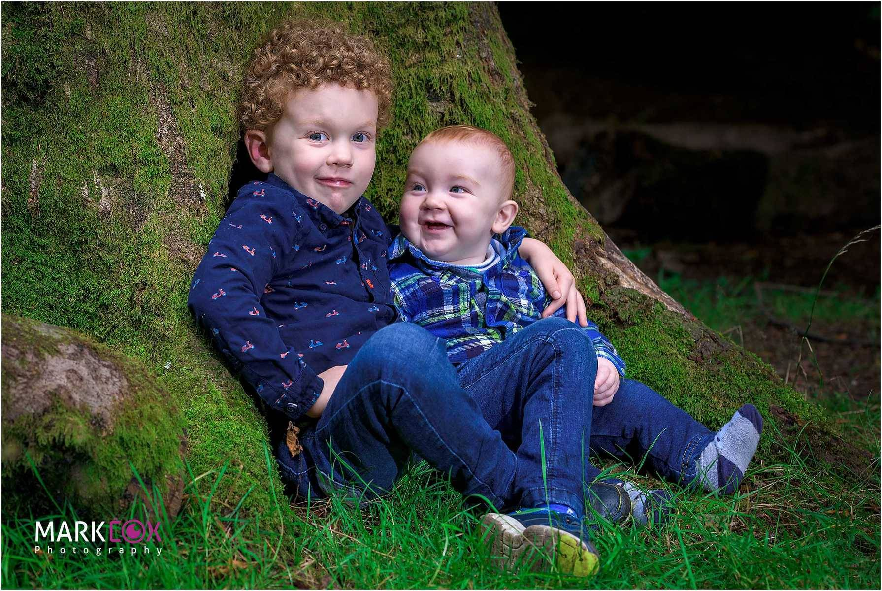 Two boys sat by a tree